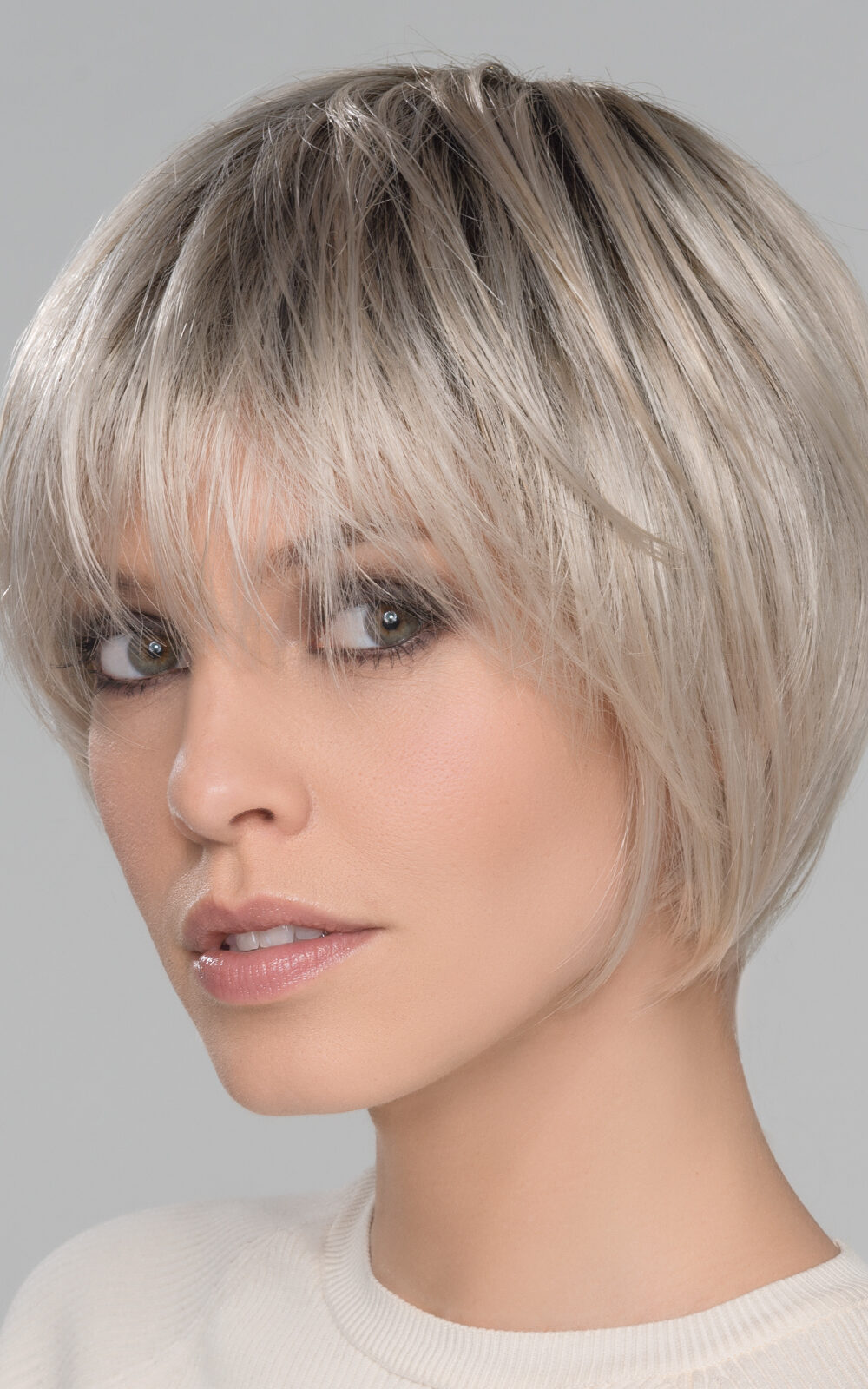 With soft layers that frame around the face. Edgy, with pieced out bangs and lots of personality
